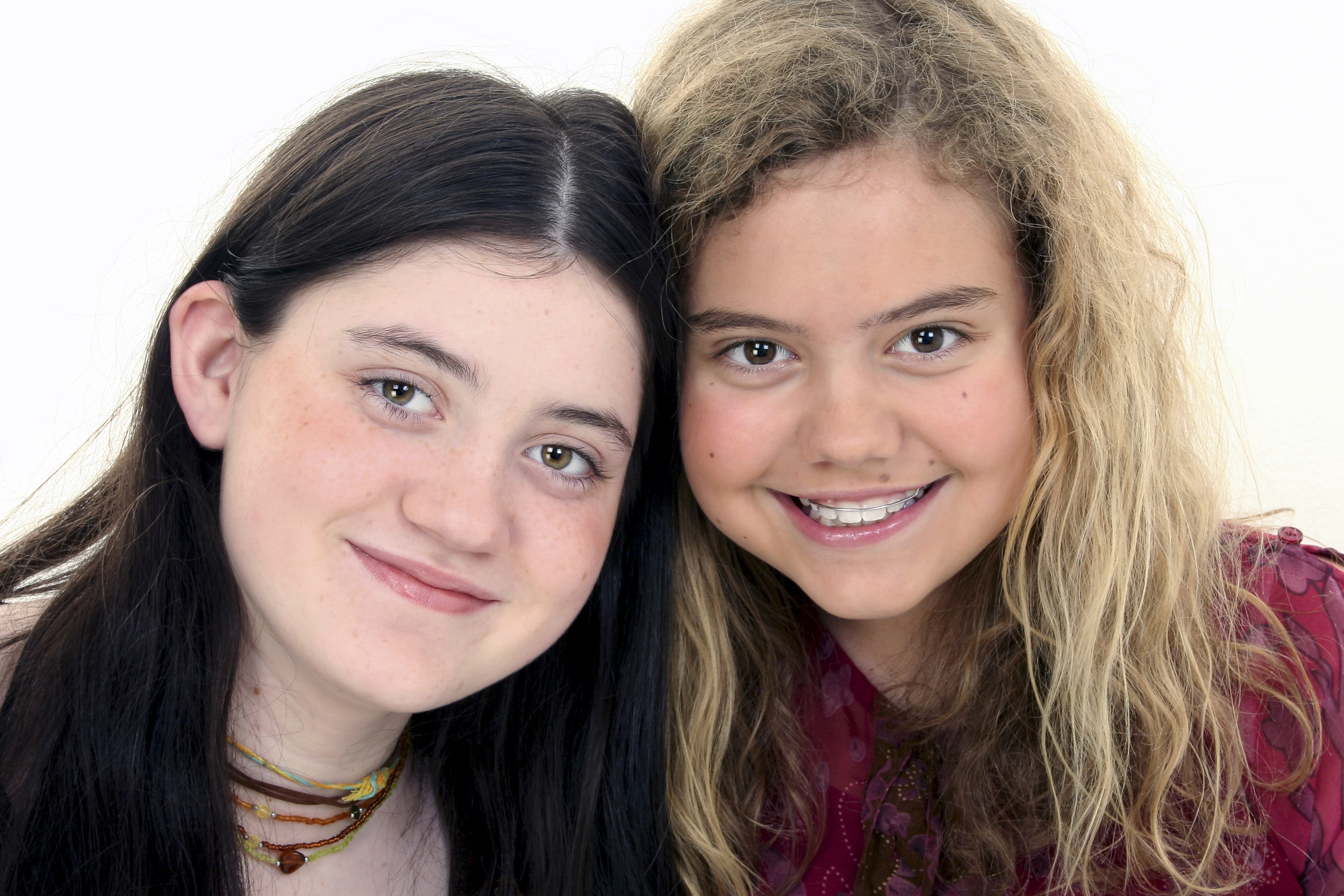 Two beautiful 12 year old friends together. Shot in studio over white.
